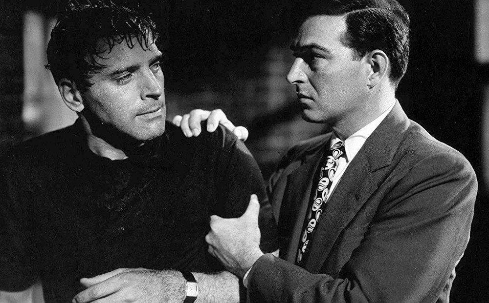 One man grips actor Burt Lancaster by his shoulder and arm.