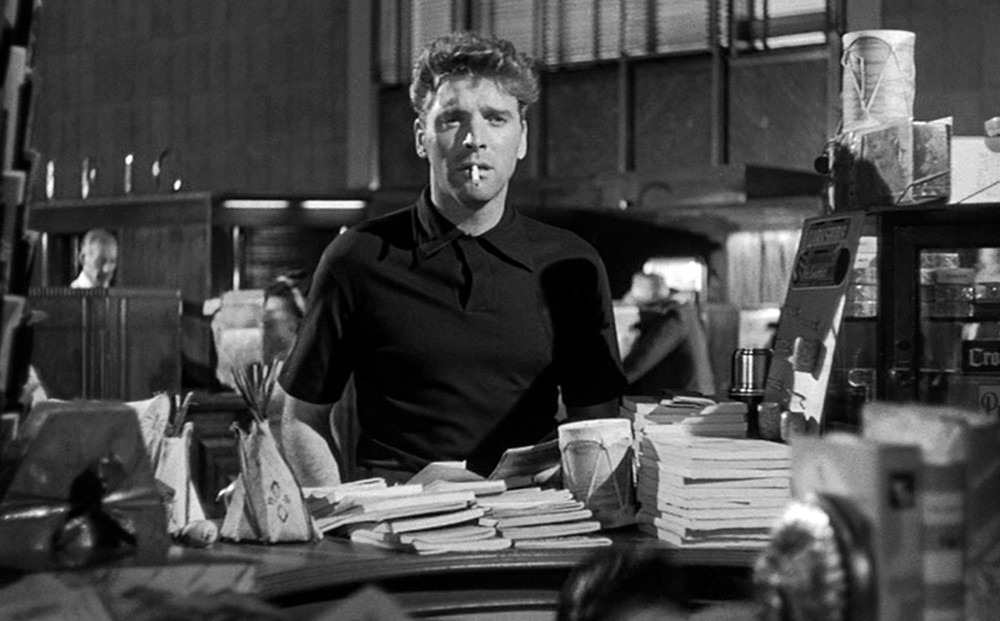 Actor Burt Lancaster sits at a desk that's covered in books, a cigarette in his mouth.