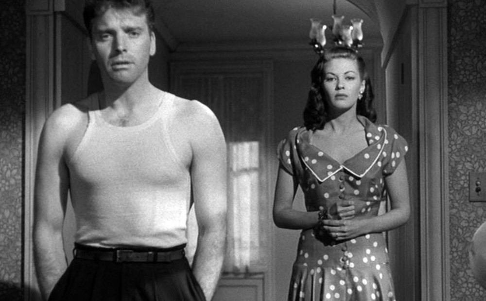 Actor Burt Lancaster wears a white tank top in the foreground; Yvonne De Carlo appears behind him.