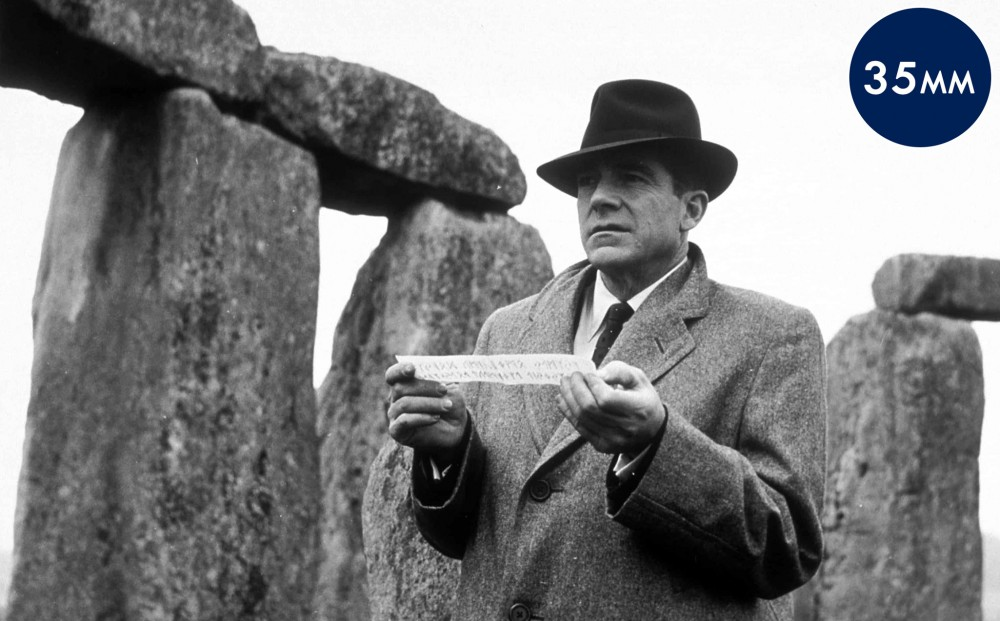 Actor Dana Andrews holds up a strip of paper that appears to be a clue, with Stongehenge in the background.