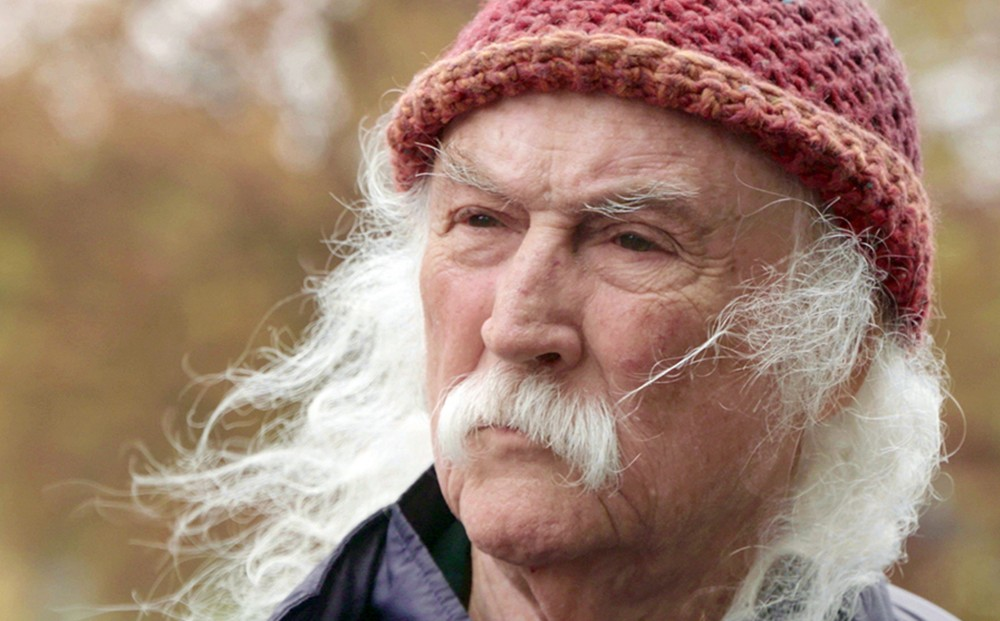 Close-up on the face of musician David Crosby with a white moustache and white hair.