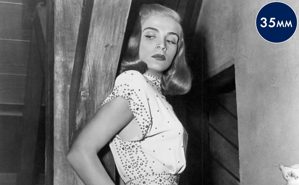 Actor Lizabeth Scott looks down from a staircase.