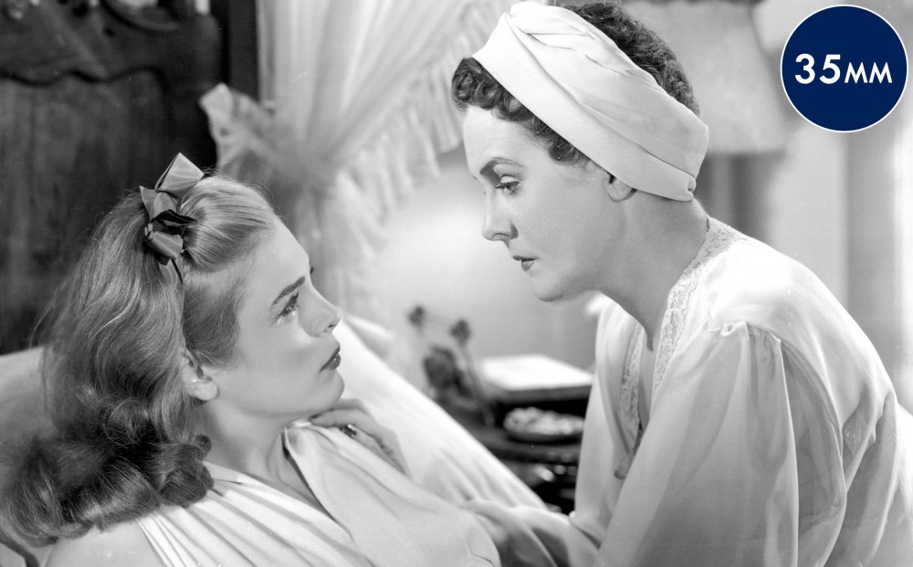 Actors Lizabeth Scott lies on a bed, and Mary Astor sits on the bed beside her.