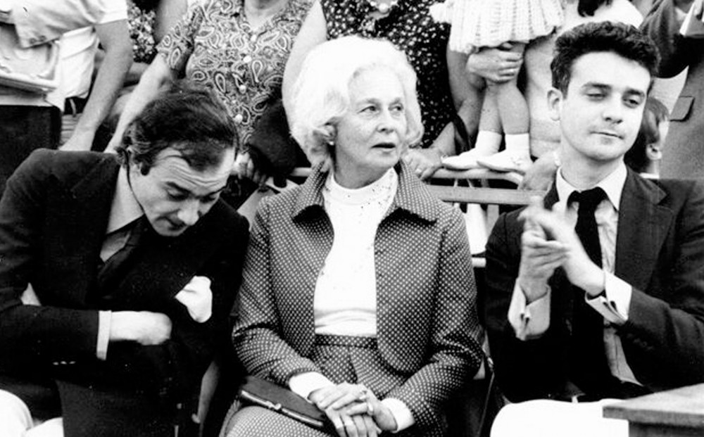 A black and white image of an elderly woman sitting between two men, as part of an audience.