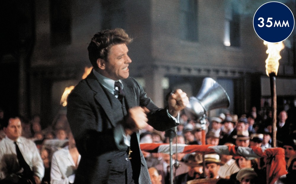Actor Burt Lancaster stands in front of a crowd of people, speaking enthusiastically while shaking his fists.