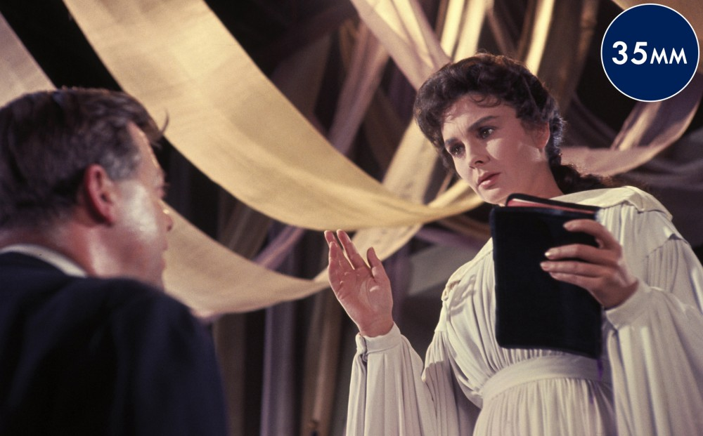 Actor Jean Simmons wears a white gown and holds a bible, speaking to a man.