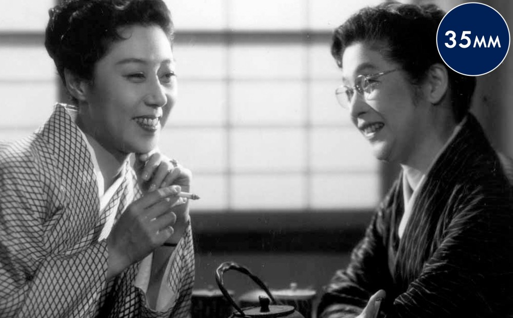 Two women sit together, smiling, while one holds a cigarette.