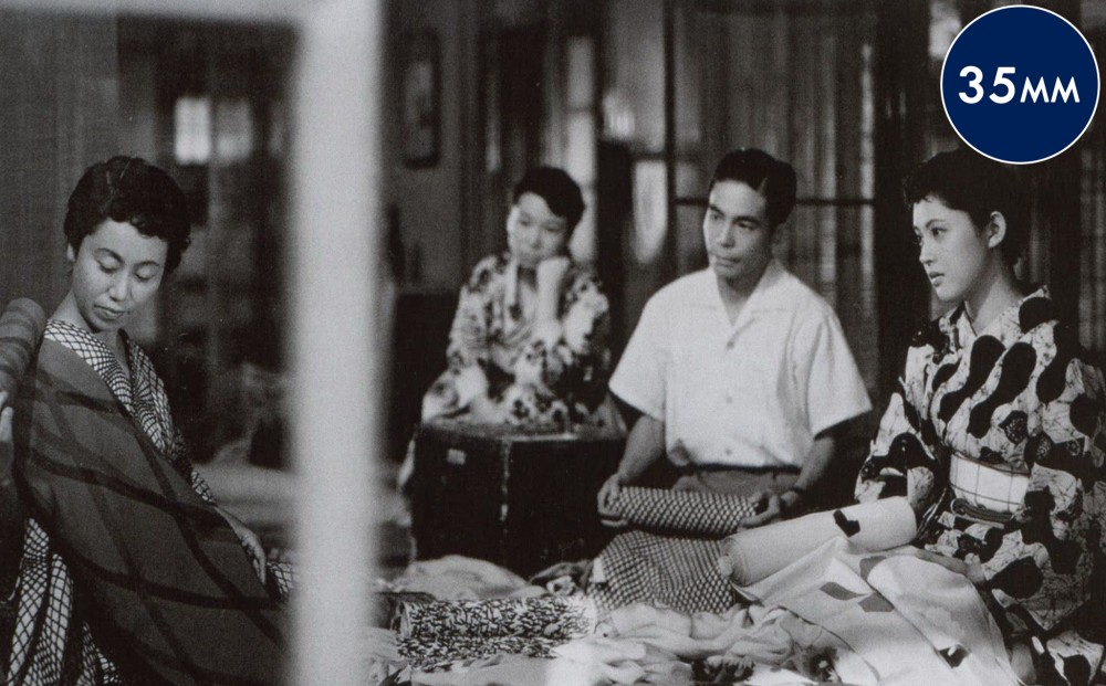 Three women sit with a man, looking at an assortment of fabrics.