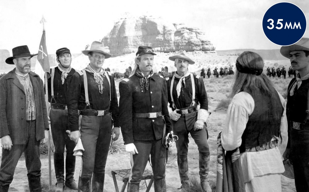Rugged-looking soldiers speak to a Native American against a southwestern landscape, including a butte.