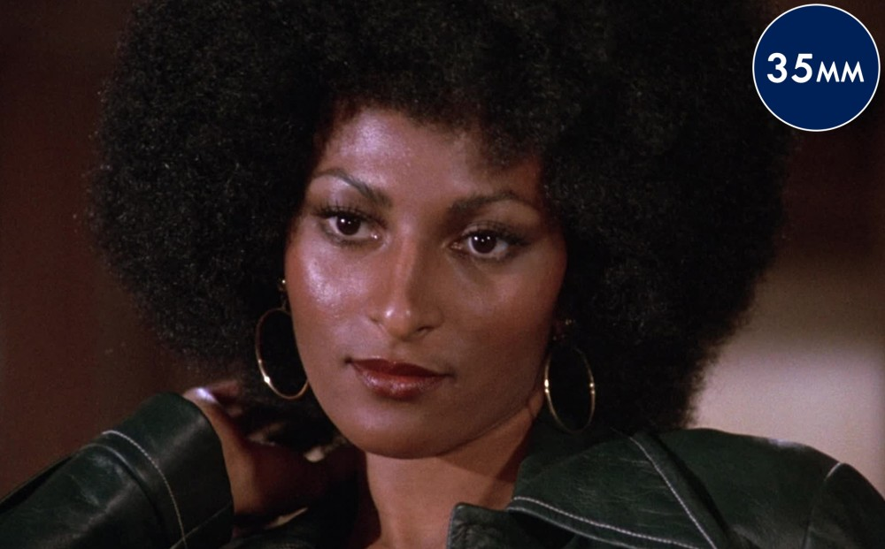 Close-up on actor Pam Grier, who wears gold hoop earrings and a green leather jacket.