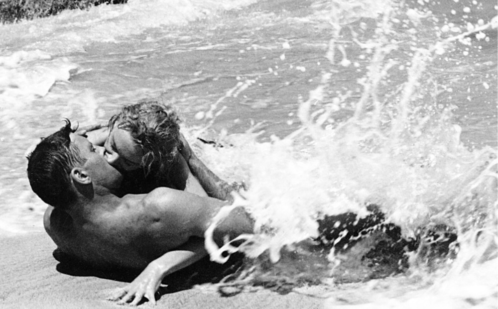 Actors Deborah Kerr and Burt Lancaster make out on the beach as a wave splashes over them.