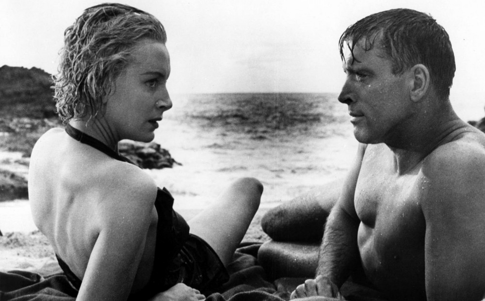 Actors Deborah Kerr and Burt Lancaster lay on the beach and talk.