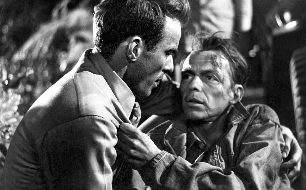 Actor Montgomery Clift holds a battered-looking Frank Sinatra in his arms; Sinatra grips Clift's shirt.