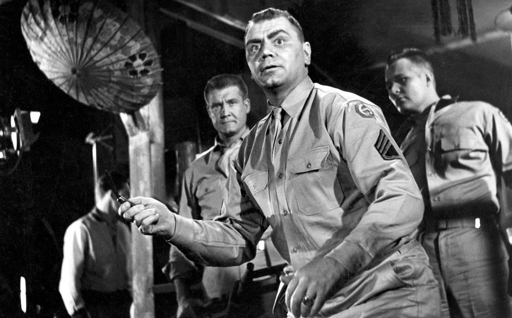 Actor Ernest Borgnine brandishes a small knife; he wears an army uniform, and there are a few other soldiers behind him.