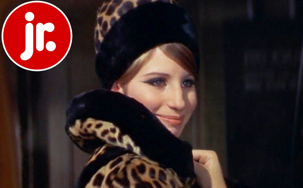 Barbra Streisand smiles, wearing a fuzzy leopard print coat and hat.