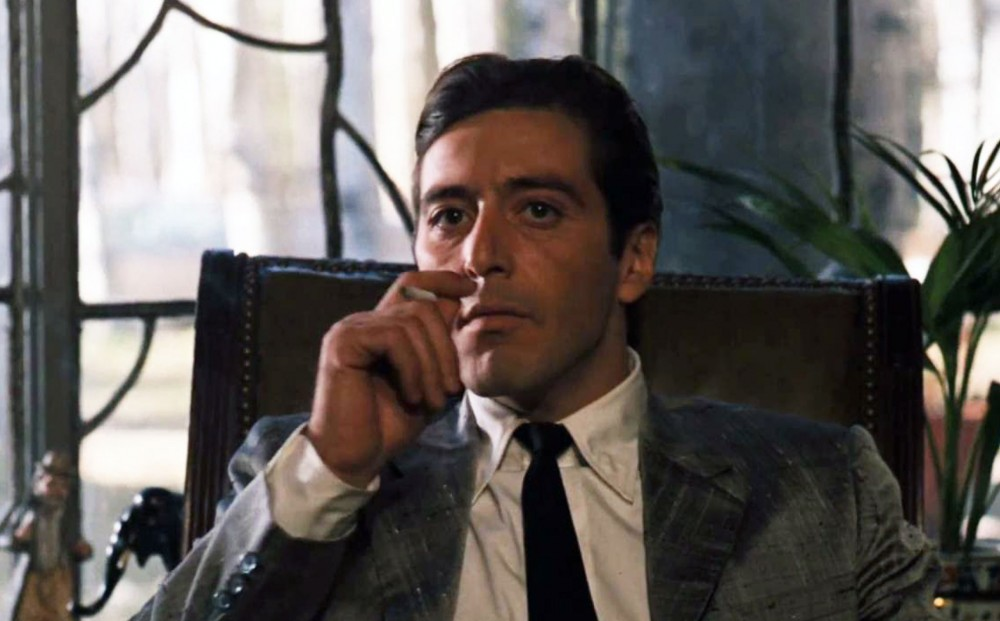 Actor Al Pacino smokes a cigarette while seated.