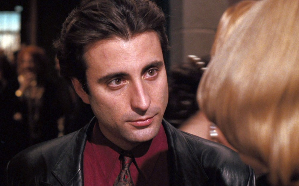 Actor Andy Garcia speaks with a blonde woman whose back is to the camera.