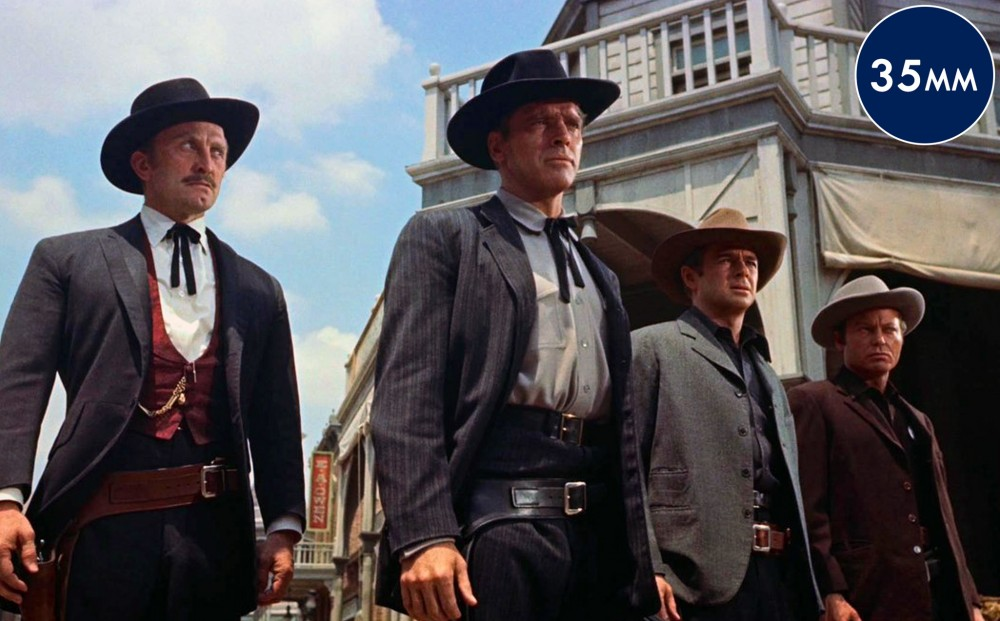 Four men stand in a row in the street of a Western town, looking uneasy.