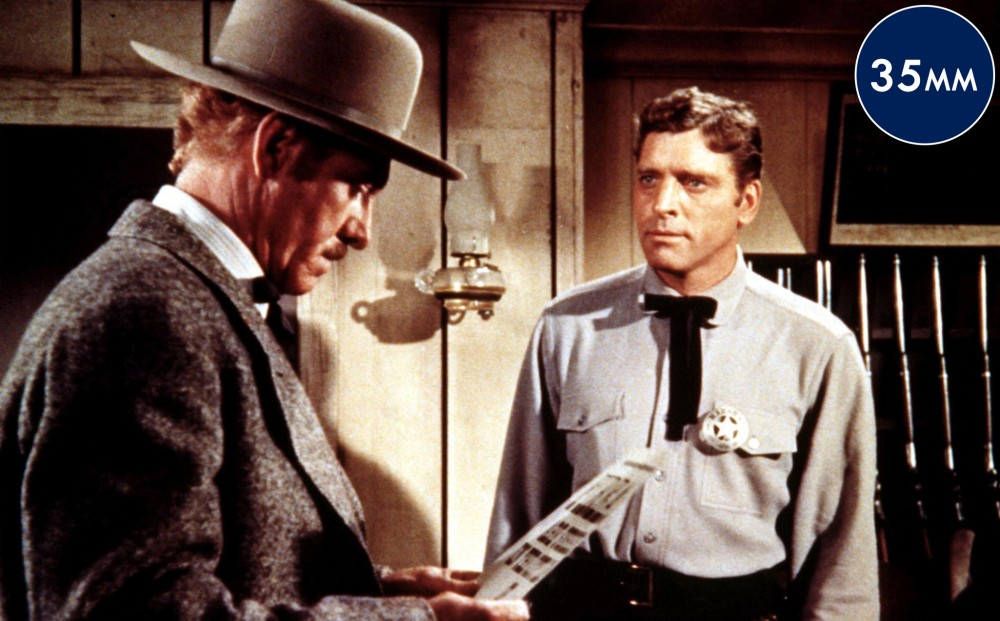 Actor Burt Lancaster looks intently at another man, who is looking down at a piece of paper.