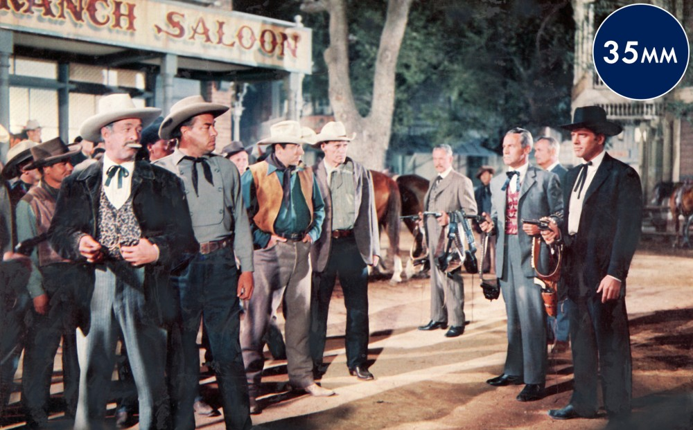 Actor Burt Lancaster and others stand in a line outside of a saloon, all pointing their guns at another group of men.