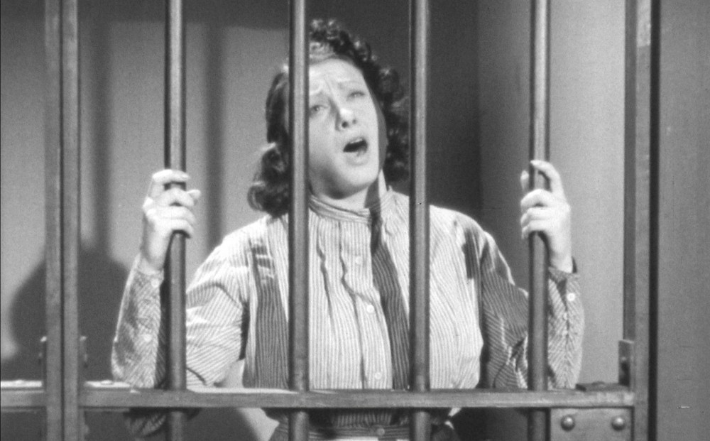 A woman behind bars holds the bars and sings.