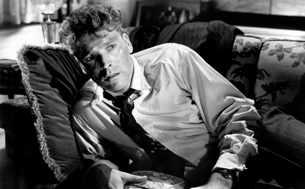 Actor Burt Lancaster reclines on a couch, wearing a tie and white button-down shirt.