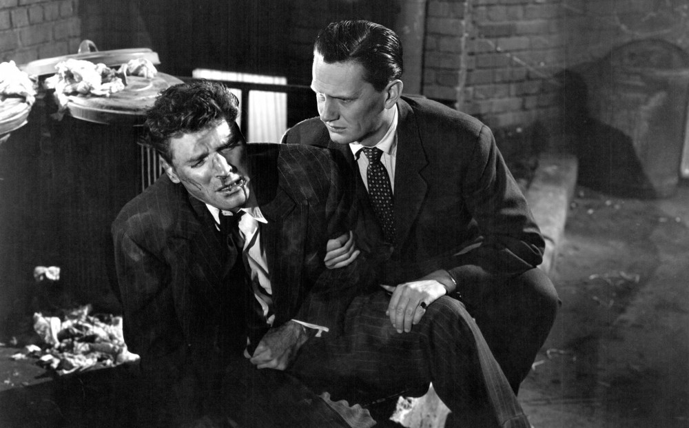 Actor Burt Lancaster sits on the ground near garbage cans, clutching his stomach as though injured; another man holds Lancaster's arm and leg.