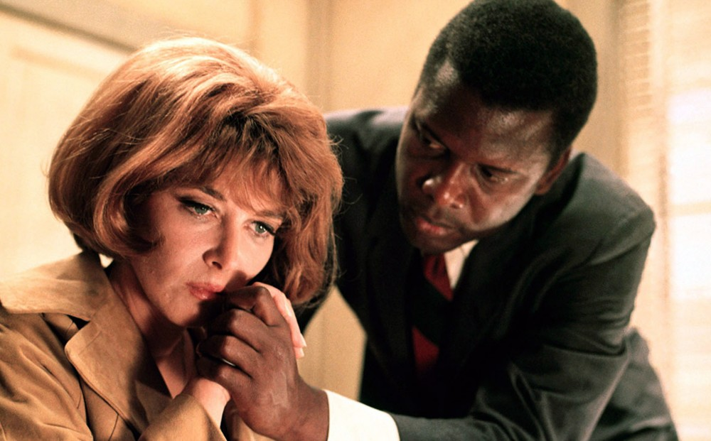 Actor Sidney Poitier looks at Lee Grant with concern; their hands are clasped.