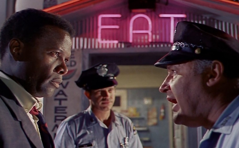 Actor Sidney Poitier speaks with a police officer, while another one observes.