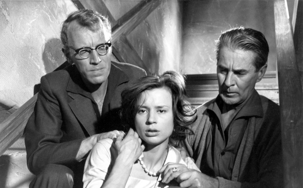 Actors Max von Sydow, and Gunnar Björnstrand sit behind Harriet Andersson, one holding her shoulder, and the other holding her hand.