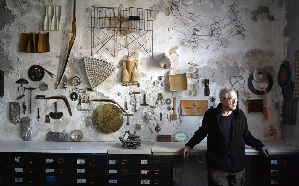 Artist and subject Jay Maisel leans against filing cabinets in his studio; objects like tools, gloves, and wires are mounted on the wall behind him.
