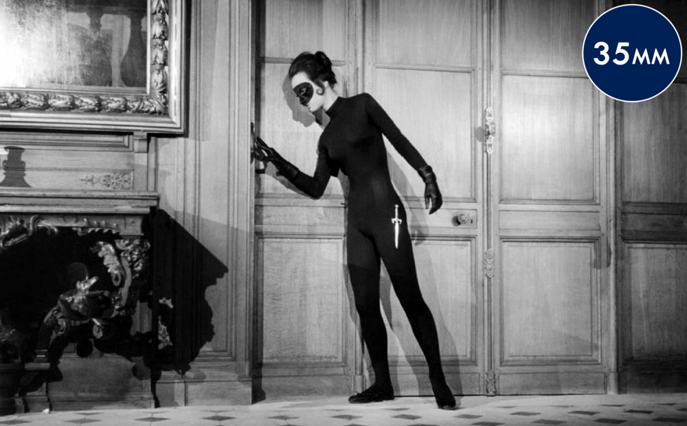 Actor  Francine Bergé lingers by a doorway, incognito in a black catsuit and black eye mask, with a dagger at her hip.