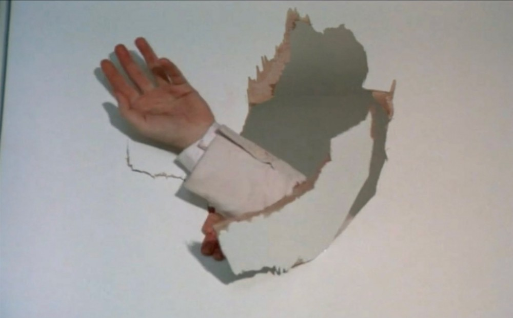 Only a hand appears, crashing through a thin white wall, leaving A hole with jagged edges.