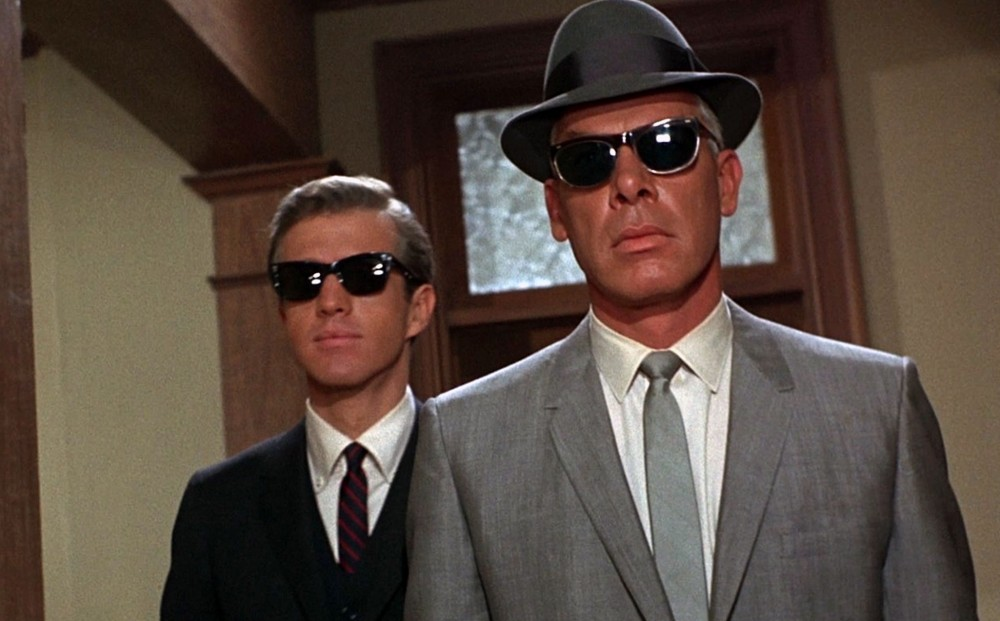 Actors Lee Marvin and Clu Gulager wear suits, ties, hats, and sunglasses.