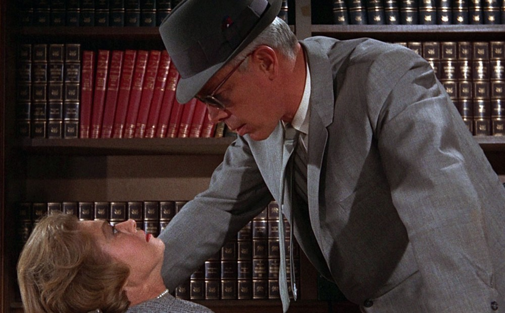 Actor Lee Marvin, wearing sunglasses, a hat, a suit, and tie, hovers menacingly over a frightened-looking woman.