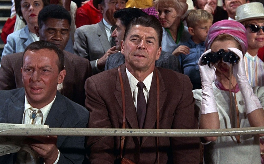 Actor Ronald Reagan sits in the audience at the race track.
