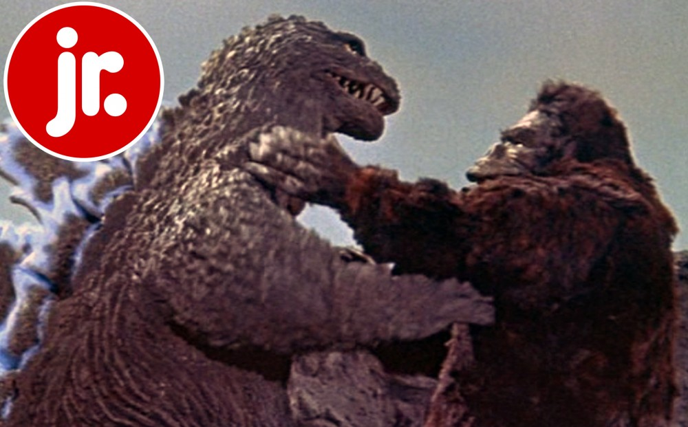 King Kong has his hands around Godzilla's neck as they fight.