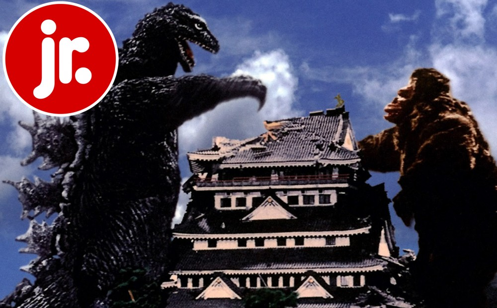 Godzilla and King Kong stand on either side of a large building.