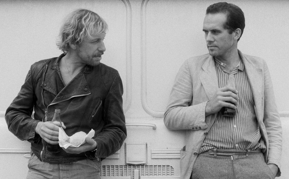 Actors Rüdiger Vogler and Hanns Zischler converse, each holding a beverage.