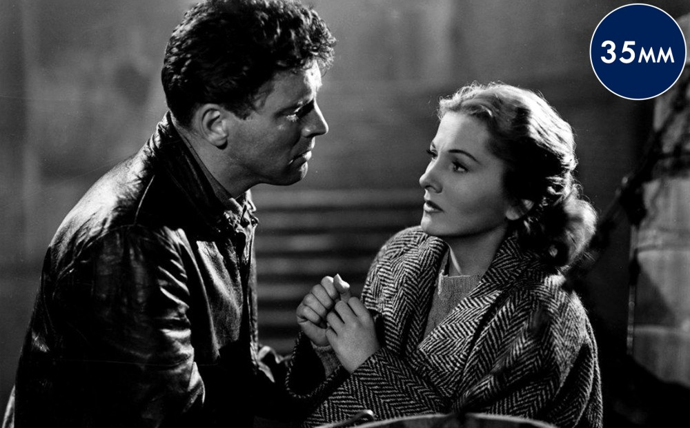 Actor Burt Lancaster holds Joan Fontaine's arms; she looks at him somewhat distrustfully.