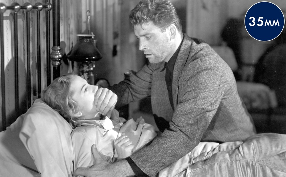 Actor Burt Lancaster covers Joan Fontaine's mouth and holds down one of her arms; she is lying in bed.