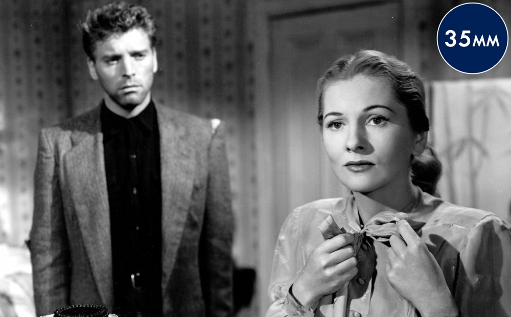Actor Joan Fontaine adjusts the bow on her collar; actor Burt Lancaster in the somewhat out-of-focus background stares at her.