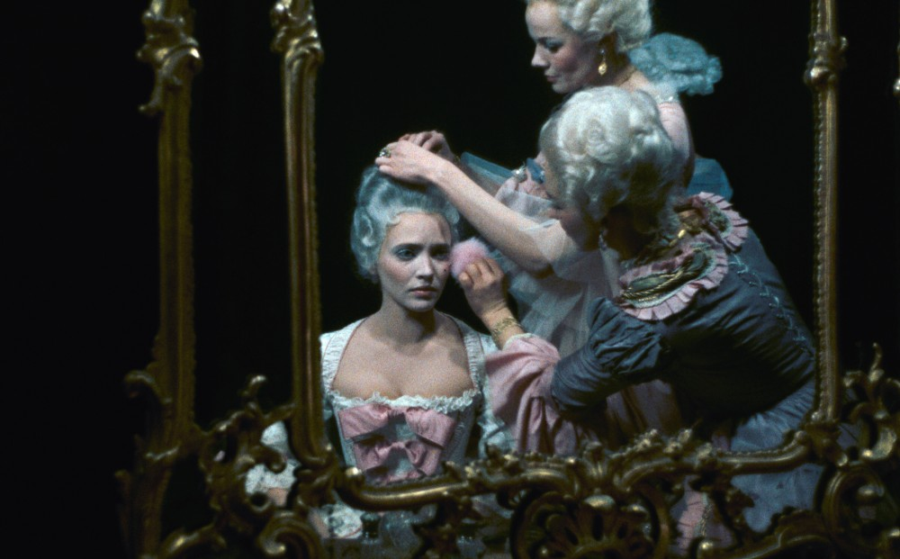 Two women put make up on and do the hair of actor Anna Karina, who wears an 18th-century-style white wig and fancy dress.