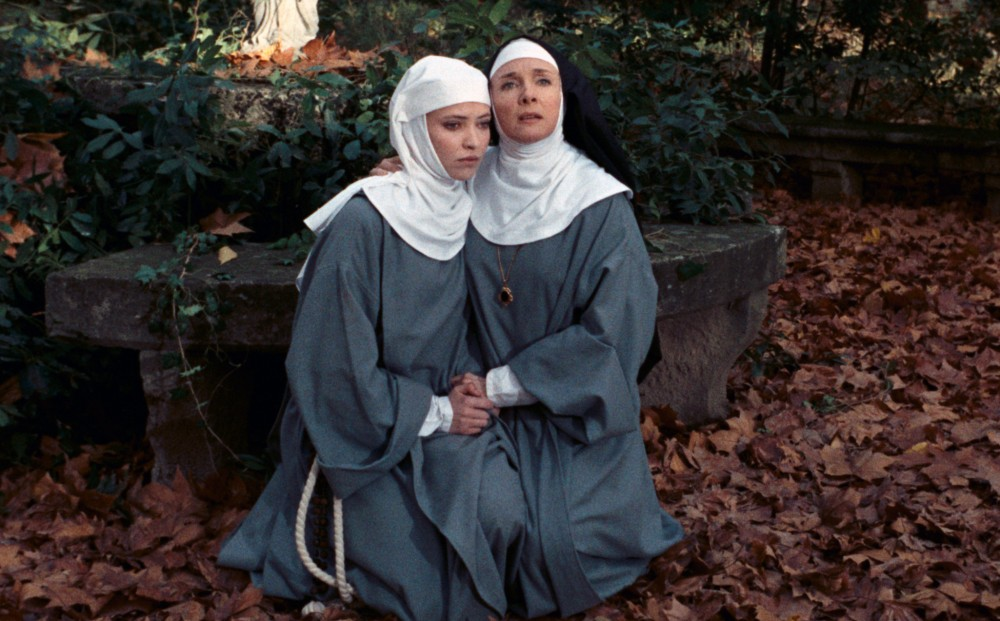 Actor Anna Karina and another nun wear habits, clasping hands and kneeling on ground that is covered in dead leaves.
