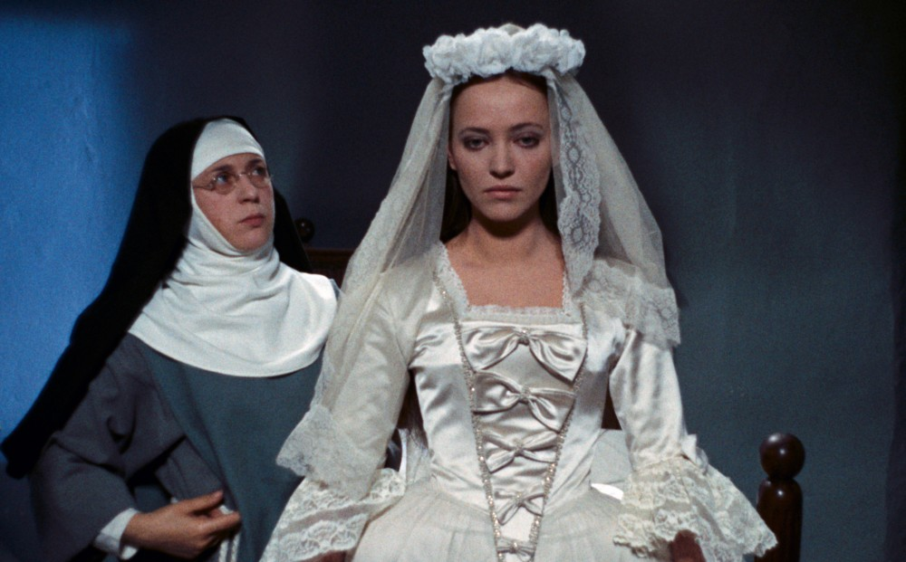 Actor Anna Karina wears a bride's gown and a nun stands behind her.