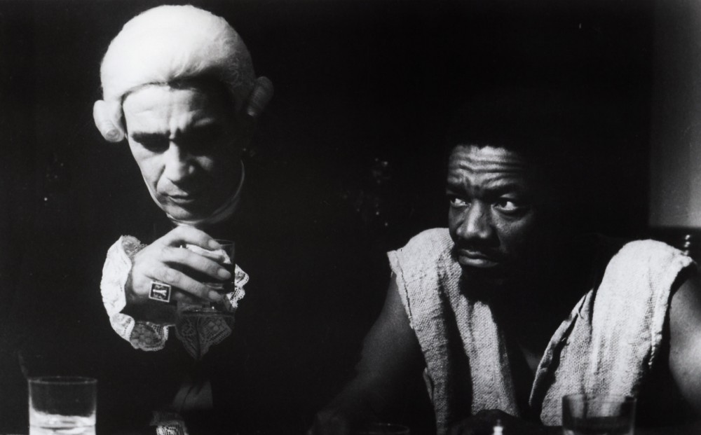 A white man wearing a wig and garb from the early 19th century sits next to a black man wearing a ragged shirt.