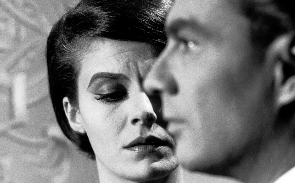 Actor Giorgio Albertazzi in profile; Delphine Seyrig looks pained behind him.