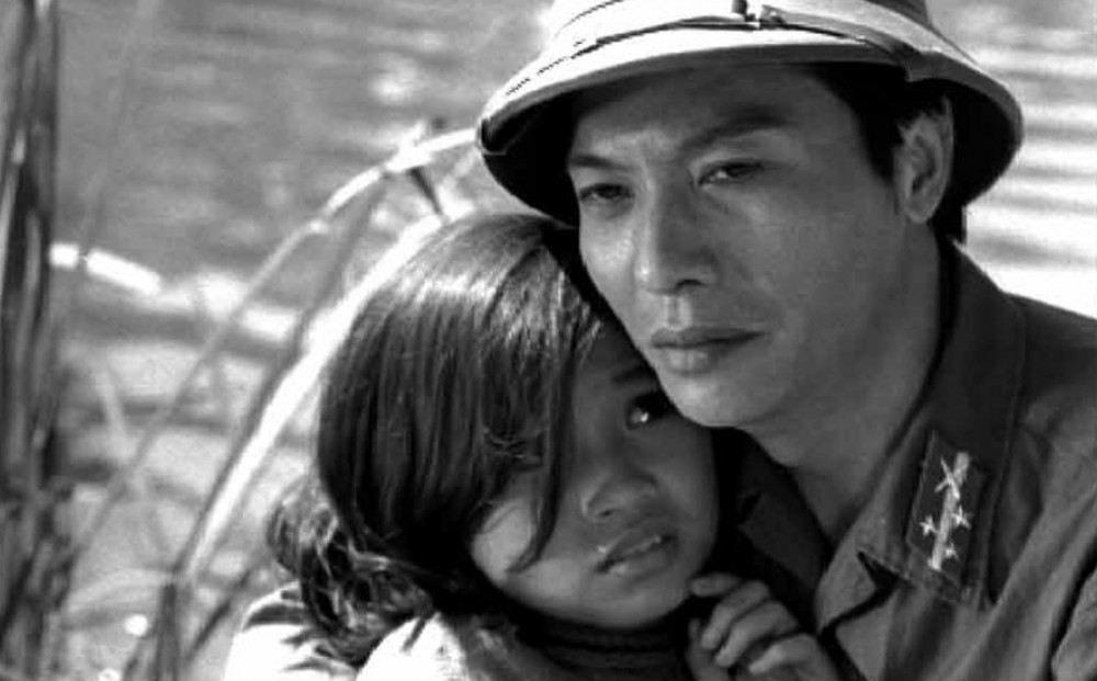 A man in uniform holds a young girl, who looks frightened.