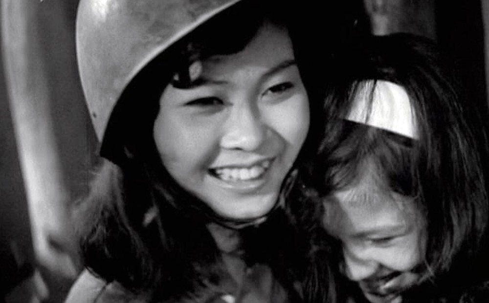 A woman wearing a soldier's helmet smiles while holding a smiling young girl.