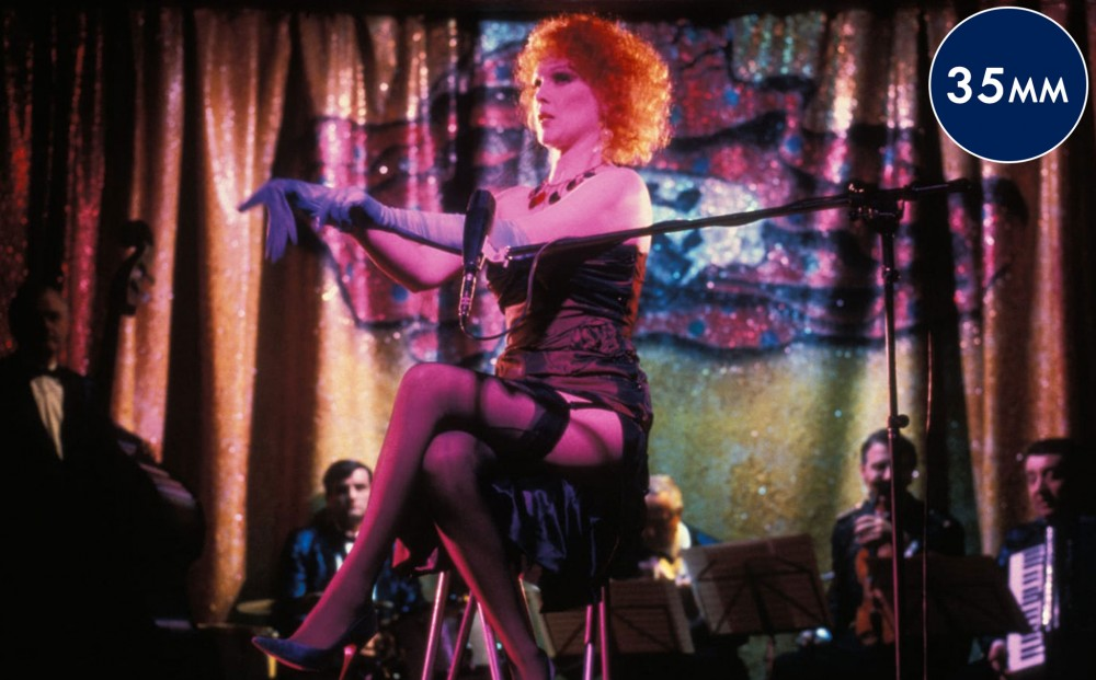 A woman sits on a stool in front of a microphone at a cabaret.